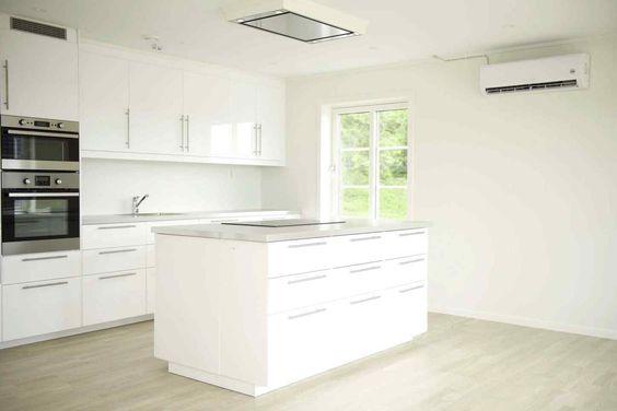 Kjøkkenet har tidsriktig innredning med hvite høyglansfronter og ...