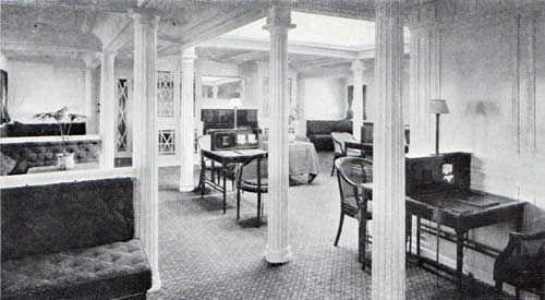 "Photo 22: Drawing Room, Second Cabin on the Cunard Lanconia and Franconia (1911). The Second Cabin Drawing Room on both ships is treated in a simple Adam's Colonial style, with white panels. The carpets and coverings are a "" veiue rose,"" which gives a broad and cheerful aspect to the room."