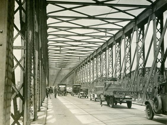 No: 585  Contributor: Marcel Gommers   Year: 1931   District: The Netherlands  Gebr. Nijman lorry on a bridge in Rotterdam    Great shot of traffic in the 'old'n days' on a truss bridge. This is prob Rotterdam; the company 'gebr Nijman' was (and is) a removal company in Rotterdam (The Netherlands). Note the bridge on the right too. Someone able to identify these two bridges? Or any of the cars here?