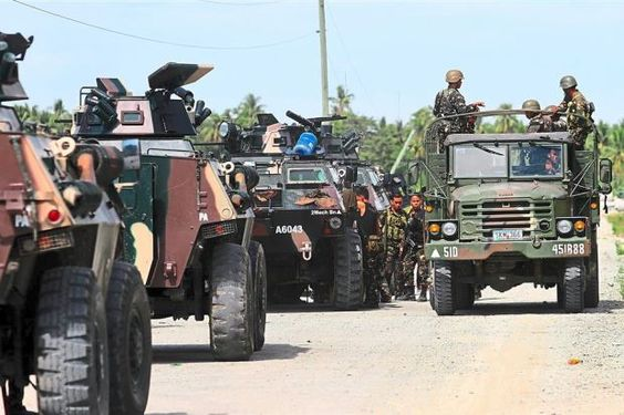 Dangerous situation: Philippine military personnel riding past armoured personnel carriers in the town of Mamasapano after Philippine security forces clashed with Muslim rebels in the south, where Marwan was said to have been killed. — AFP