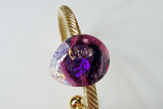 Gota em Ametista, é uma pulseira de metal banhado a ouro adornada com uma gema feita artesanalmente em estilo murano com uma mescla de vidros importados.  As cores mais aparentes são o lilás, roxo e dourado. O dourado provém do uso de vidro dicroico que tem a característica de refletir múltiplas cores. R$114