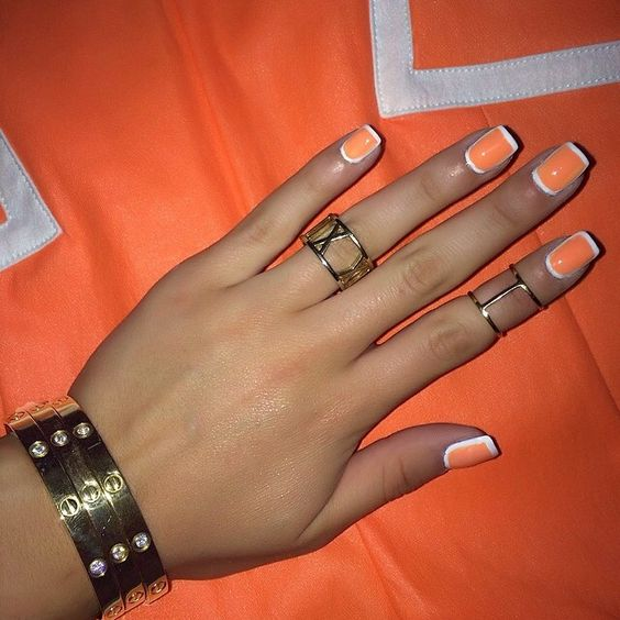 Orange nails with white outline.