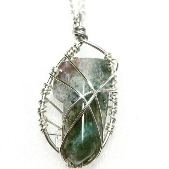 Silver caged ocean jasper pendant on black rope necklace.