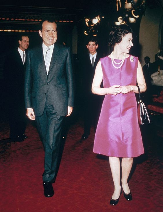 The Queen, in a fuchsia dress, walks beside U.S. President Richard Nixon. via…