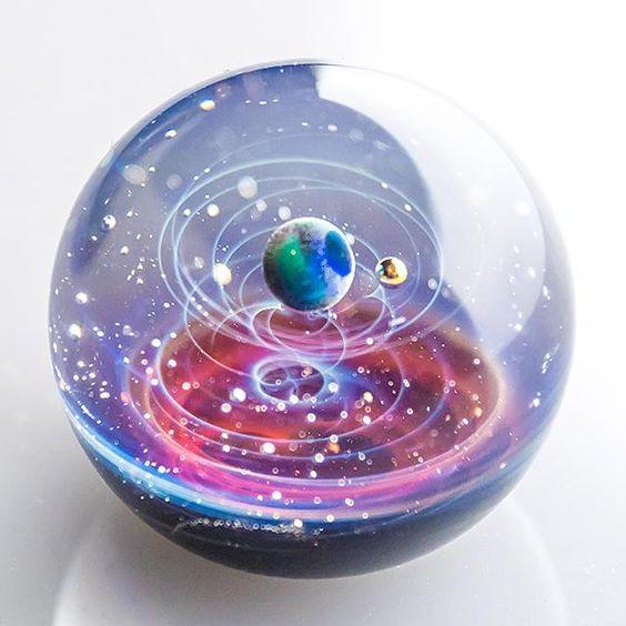 「まるでガラス玉の中に小さな宇宙空間が広がっているかのよう!」と、SNSなどで話題を呼んでいるアクセサリーがある。その名も、「宇宙ガラス」。アーティストの戸水賢志さんが制作している耐熱ガラス製のペンダントトップ&オブジェだ。一つ一つハンドメイドで作られており供給量が限られることもあって、Web抽選で定期的に一定数販売されているが、毎回応募が殺到するほどの人気だという。いったい、どんな作品なのか。また、どうやって作られているのか。「宇宙ガラス」を手がけるアーティストの戸水さんに話を伺った。