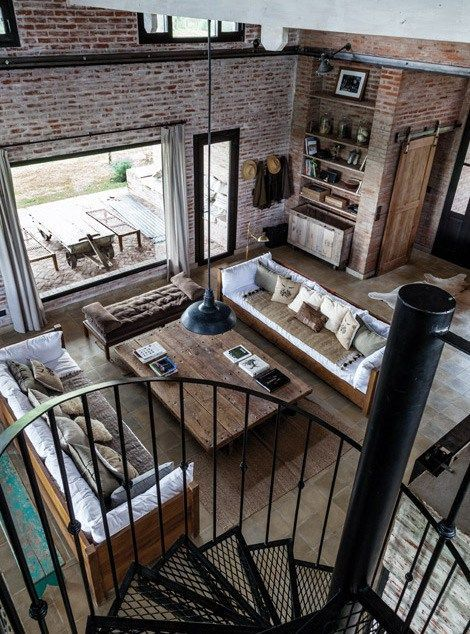 An amazing space with defined areas through the use of furniture. The exposed brick provides warmth and texture to the space and the spiral staircase introduces an industrial feel to the space.