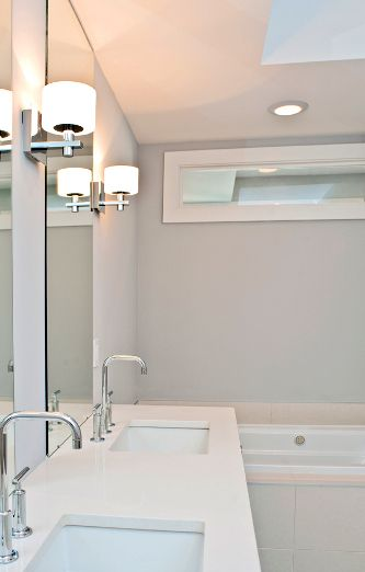Transom window above bathtub area to allow natural light into a bathroom located in the interior. Transom window above bathtub area to allow natural light into a