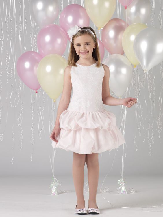 Sleeveless taffeta and tulle above-the-knee A-line dress with jewel neckline, dropped waist tulle overlay bodice with scattered lace appliqués, full double tiered bubble taffeta skirt with tulle overlay. Sizes: 4 – 16