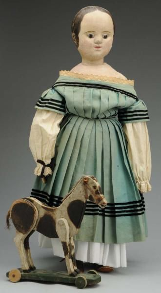 """Izannah Walker Cloth Doll. Made by Izannah Walker in Central Falls, RI. All cloth with molded head, brown painted hair with 3 corkscrew curls at side in front of ears, applied ears, molded eyeballs, feathered eyebrows, dark painted eyes, period aqua wool dress, antique shift and brown leather shoes. Size 24"""" T."""
