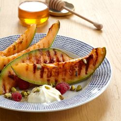 Grilled cantaloupe with honey-sweetened cream, raspberries, and pistachios.  #foodgawker