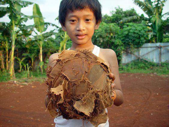 Um Miúdo de Jacarta segura UMA bola de futebol velha e esfarrapada.