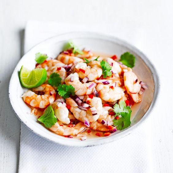 Bestrooi de garnalen met zout en laat 1 minuut staan. Voeg de citroen- en limoensap, chilipeper, rode ui en tabasco toe toe en marineer de garnalen 10 minuten. Serveer met koriander en limoen.
