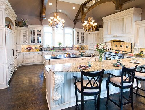 White kitchen double islands dark floors panelled for Perfect kitchen layout with island