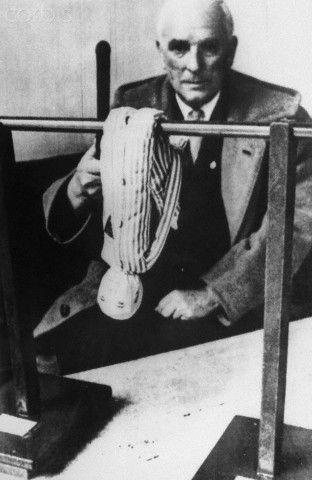 Paul Leo Seidel, of Munich, former inmate of the Auschwitz Extermination Camp, displays a model of the 'Boger Swing.' It was a torture method devised by Wilhlem Boger, one of the defendants at the Frankfurt Auschwitz Trials held from December 20, 1963 to August 19, 1965. According to testimony of Auschwitz survivors, the prisoner's hands were tied in back and their legs put through this loop. They were then made to 'swing' by Boger using truncheon or whip. Rights Managed, Stock Photo Corbis