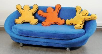 Keith HARING (1958-1990),  Canapé de forme corbeille recouvert de velours bleu, monté sur quatre ressorts, et agrémenté de quatre coussins qui ont la forme des personnages emblématiques de Keith Haring. Edition Bretz circa 2000. Plaque de l'éditeur. H. 88 cm L. 245 cm P. 150 cm