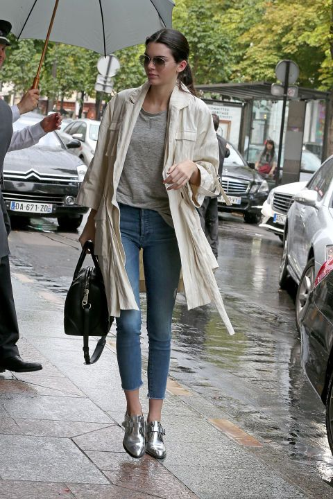 Kendall looks chic on a rainy day in Paris in a lightweight trench coat, gray tee, and skinny jeans.:
