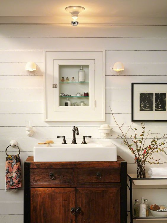 Farmhouse Bathroom: White sink inset in antique dresser. Beautiful slat wall with inset medicine cabinet.