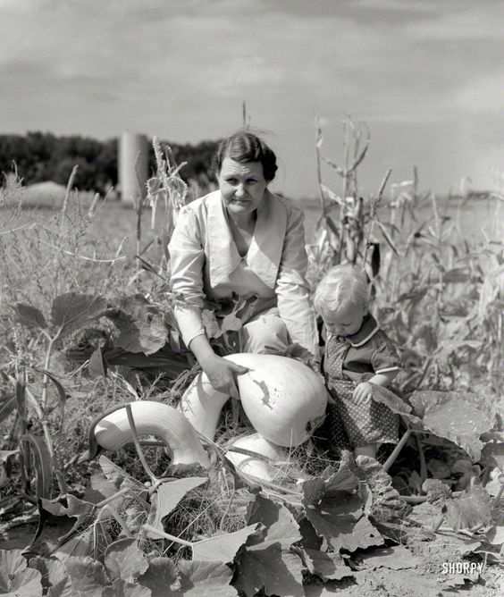 "October 1939. ""Mrs. Calvin Brown, wife of Farm Security Administration borrower, with grandson in garden near Eaton, Colorado."""