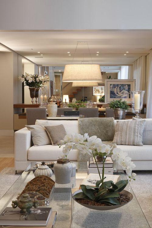 sala de esatr decorada no estilo contemporâneo, com sofá branco, almofadas em tons neutros, espelho grande atrás do sofá, vaso com flor branca em cima da mesa de centro de vidro transparente