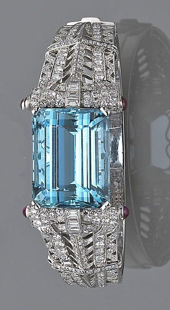 A retro aquamarine and diamond bangle bracelet, ca. 1945 - the hinged bangle with a top section centering a rectangular-cut aquamarine with openwork shoulders set with single, old European and baguette-cut diamonds and cabochon ruby detail; aquamarine weighing approximately: 50.00 carats; estimated total diamond weight: 4.80 carats; mounted in eighteen karat white gold; diameter: 2½in.