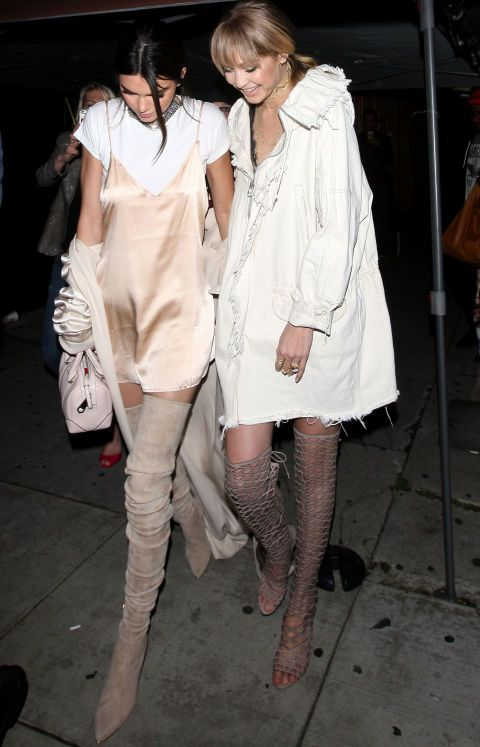 After the MTV Movie Awards, Kendall and Gigi slipped into complementary looks that were a little more comfortable... yet, just as chic. We're living for Jenner's pink silk slip dress layered over a white T-shirt and paired with thigh-high boots.: