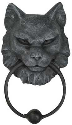 """For cat lovers everywhere we bring you this door knocker with a fierce and stern looking cat head holding the knocker. Knock if you dare! Cold cast resin. 7"""" x 4 12"""" x 2"""""""