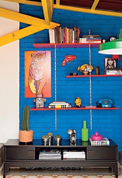 """A parede de tijolos aparentes já existia no terraço do apartamento do consultor de imagem Geovane Pedro de Bertoli. """"Inspirado nos filmes do espanhol Pedro Almodóvar, escolhi este azul para contrastar com as outras cores fortes, como o amarelo"""", diz"""