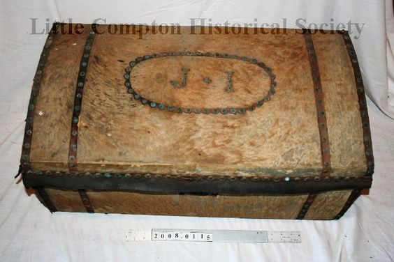 """Trunk made of light tan animal hide. Metal wire handles on opposite ends of trunk. Top lid of trunk is slightly domed. Top, front and sides are covered in decorative pattern of rivets. At top center of lid, rivets spell out the intials """"J. I"""". These initials may stand for John Irish. At front is a large metal closure. Interior is lined with deteriorated fabric. Old tag in trunk reads """"John Irish Trunk ( not first J. Irish) From Theodora W. Peckham 19"""