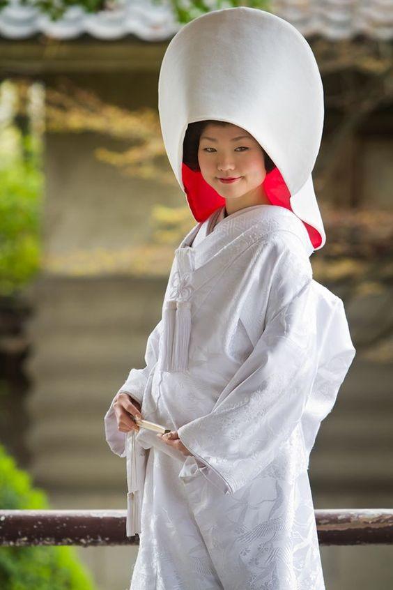"""Joven japonesa vestida de novia con kimono blanco y un wataboshi (en la cabeza) que según la tradición """"esconde"""" a la novia detrás y representa la modestia de la novia. Sería lo equivalente a un velo en las bodas occidentales"""
