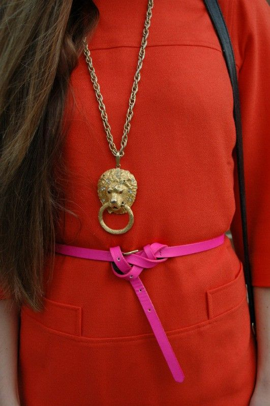 orange dress with pink skinny belt and ornamentation necklace