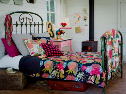 Iron bedstead, pretty quilt, wood floors, pink side table and a wood-burning stove; what more could you want?