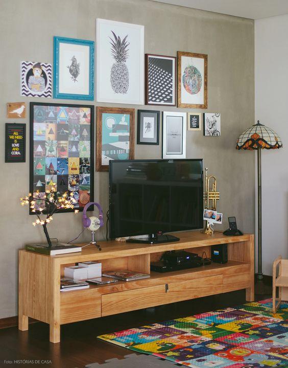 Na falta de uma estante grande, aposte em pequenos racks e deixe a decoração atrás da TV por conta dos quadros e molduras: