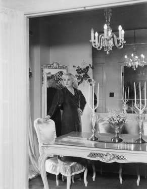 Actress Mae West ushers in a more romantic look, with glimmering glass chandeliers, a detailed table... - Moviepix + Getty