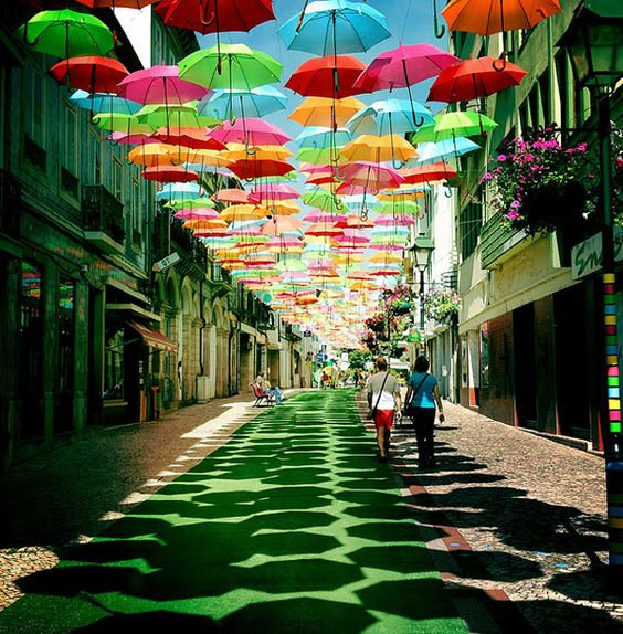 Colorful umbrellas suspended over a street in Portugal.
