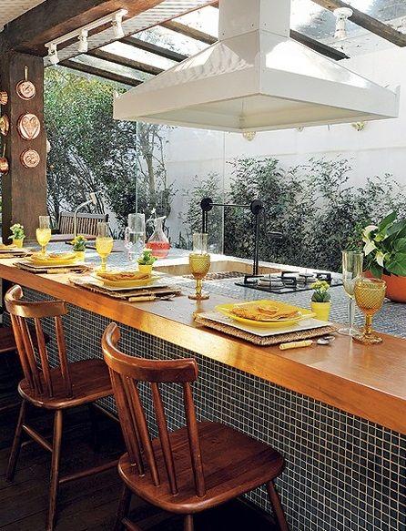 Iluminação em trilhos sobre pórtico de madeira que fica em cima da mesa. Do outro lado, o fogão cooktop.