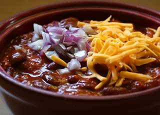 Great for Thanksgiving leftovers, this turkey chili recipe uses shredded turkey meat, kidney beans, onion, garlic, tomatoes and chili.  Garnish with grated cheddar and chopped red onion.
