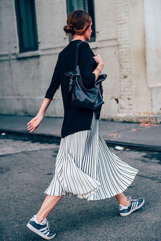 Foto de street style de mulher morena usando look despojado com tricot preto, saia midi de listras preta e branca, bolsa de couro e tênis adidas gazelle azul: