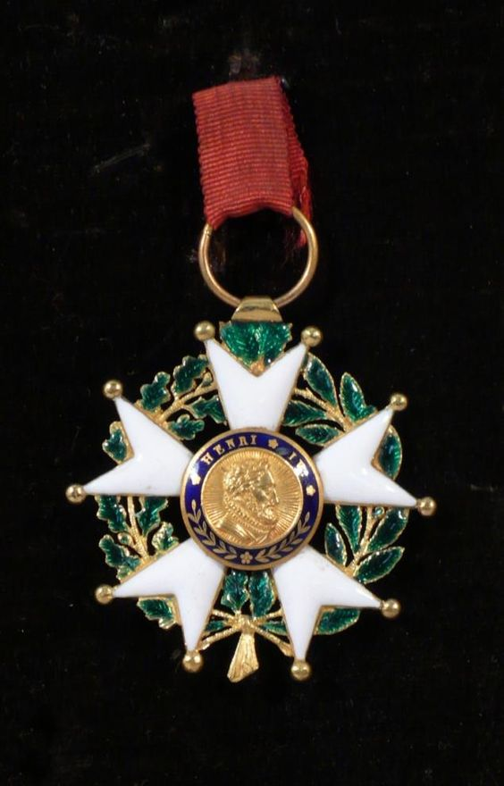 France - Ordre de la Légion d'honneur, fondé en 1802, étoile d'officier du modèle Louis-Philippe, en or et émail (éclats au feuillage), manque la couronne, poinçon à la tête d'aigle, fragment de ruban miniature. Haut. 43, Larg. 42 mm. TB.