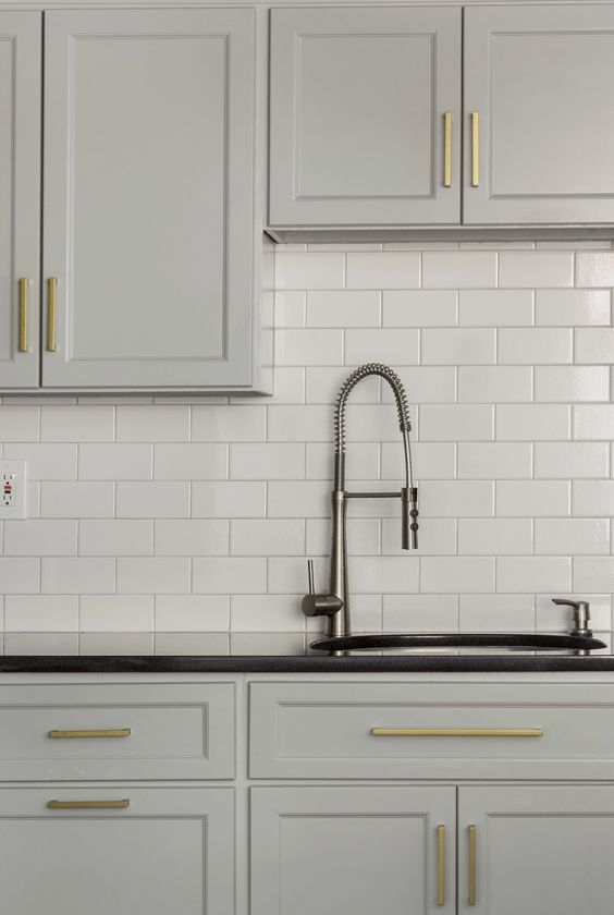 brass modern cabinet hardware gray cabinets black countertop white subway tile- Design Manifest