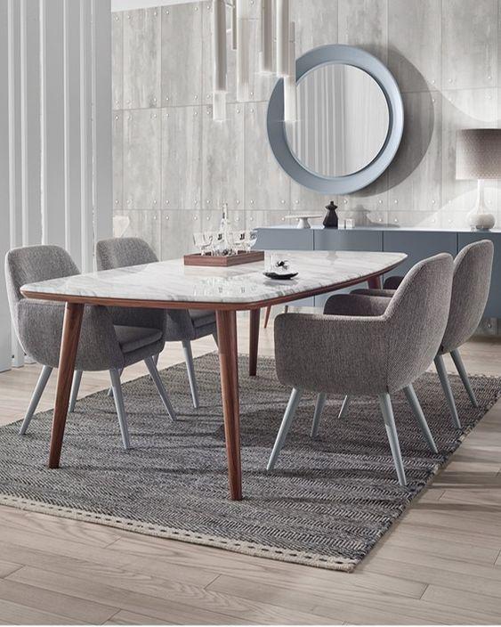 Mesa de comedor con tapa en marmol y patas en madera. La tapa tiene forma barril que se llama a las mesas rectangulares que tienen los lados curvos y las cabeceras rectas.