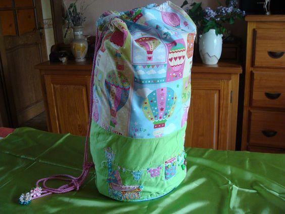 """Sac à linge pour bébé. Appliqué """"corde à linge"""" et tissu patchwork. Cordon rose et embouts fleurs en ruban."""