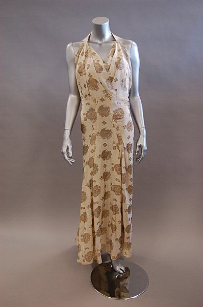 A brocaded ivory silk halter-neck gown, probably Callot Soeurs, 1937, woven with hydrangea and leaf repeats, with pleats of fabric over the bust, bias cut panels at the hips, slightly trained skirt, bust 96cm, 38in