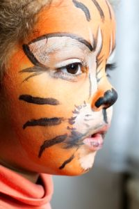 Little girl with her tiger face paint daydreaming