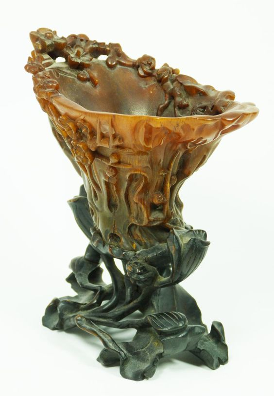 """CHINESE CARVED RHINOCEROS HORN FLORAL LIBATION CUP A finely carved antique Chinese rhinoceros horn floral libation cup having a figural stump and floral vine design throughout. Figural branch form handle. Includes fitted wooden flora form and lily pad base. Qing dynasty period. Horn measures 4"""" height x 6"""" length x 3 1/2"""" depth + 2 1/8"""" base height (10.1cm x 15.2cm x 8.9cm + 5.4cm). Total horn weight of 249 grams."""