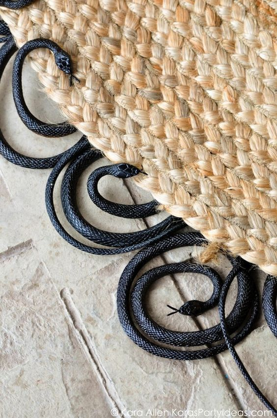 DIY painted rubber snake rug! Creepy for Halloween! Charger, table runner and other halloween decor, too if you click on the image! Via Kara Allen | KarasPartyIdeas.com #halloweenpartyideas #halloweendecorating