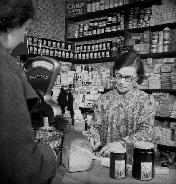 Mrs Forsyth collects her jam ration from the shopkeeper in the village of Rowney Green in Worcestershire, as the shopkeeper checks off the coupons in Mrs Forsyth's ration book. The jam on sale was made by the local Women's Institute.