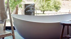 CASA TRÈS CHIC: ÁFRICA DO SUL - UMA CASA DE FÉRIAS. Modern bathtub in front of open window.