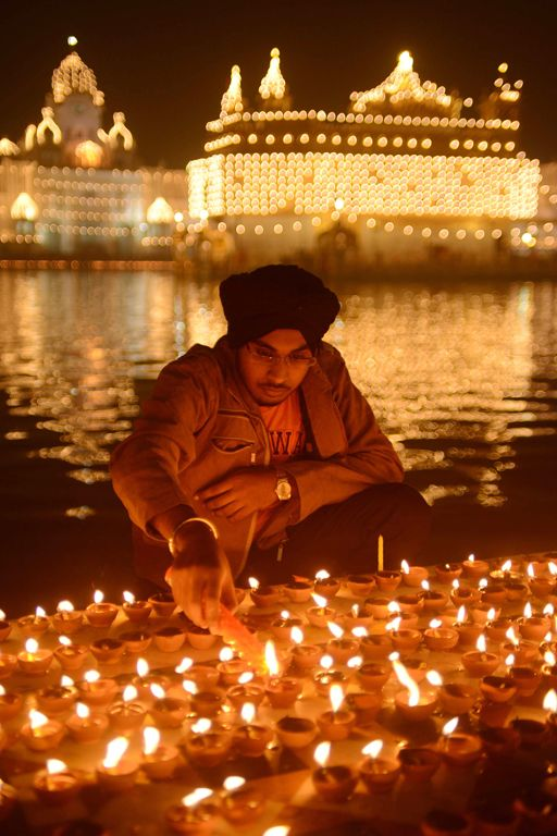 A man lighting candles for the beginning of Diwali, the festival of lights. for more great ideas visit www.thepartyguide.co.uk