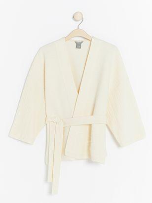 Vit kofta i kimono-stil med vida, croppade ärmar och knytskärp i midjan som passar hela året om. Bär den ihop med dina favoritbyxor eller med ett par shorts på sommaren.