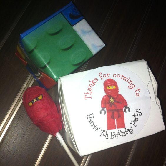 Ninjago party favors -sucker wrapped in crape paper with eyes -Chinese to go box with Lego crayons from eBay and ninjago bottle cap necklace from etsy -slinky wrapped in Lego image printed from computer